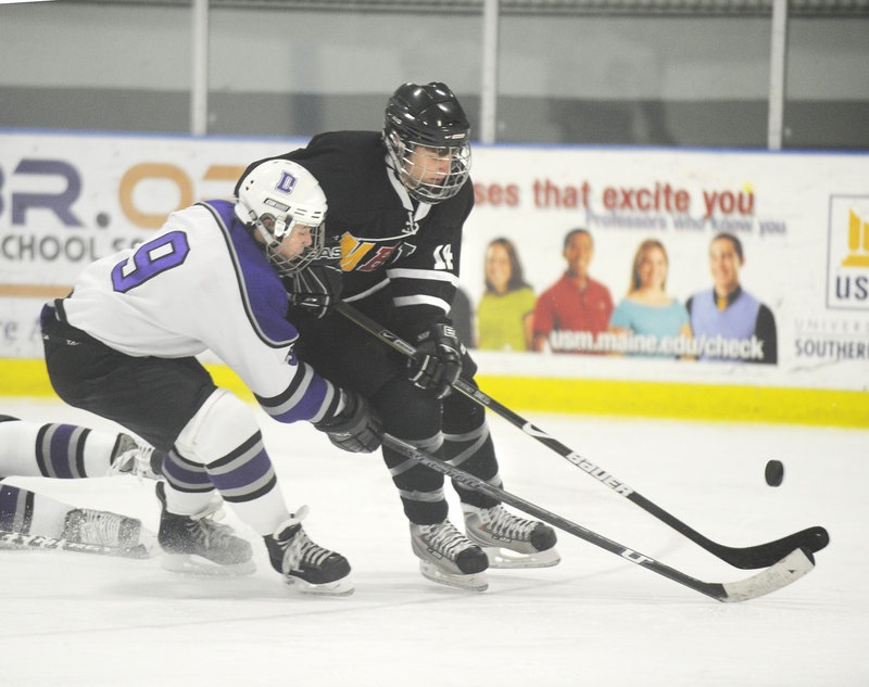 In this January 2010 file photo, Monday, former Deering High School player A.J. Asbury, (No. 9, left), pressures the puck. Deering High School has received a waiver to merge with Portland High School for boys hockey.