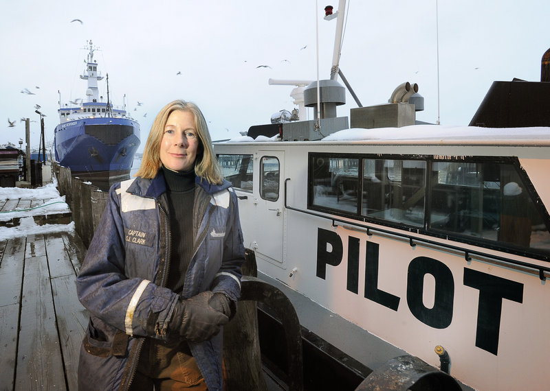 Capt. Susan Clark of Portland Pilots Inc. is seen in January alongside one of the boats she used to board the oceangoing vessels she piloted into Portland Harbor.