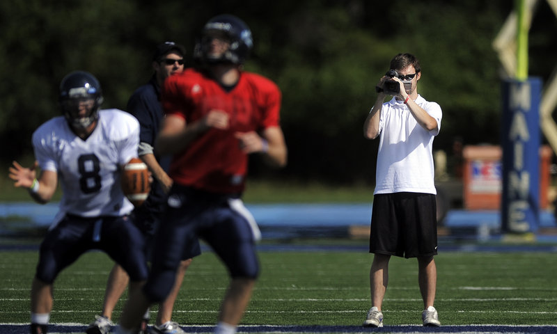 Jimmy Bump, a former Cape Elizabeth quarterback, films the University of Maine football team's recent practice at Morse Field in Orono.