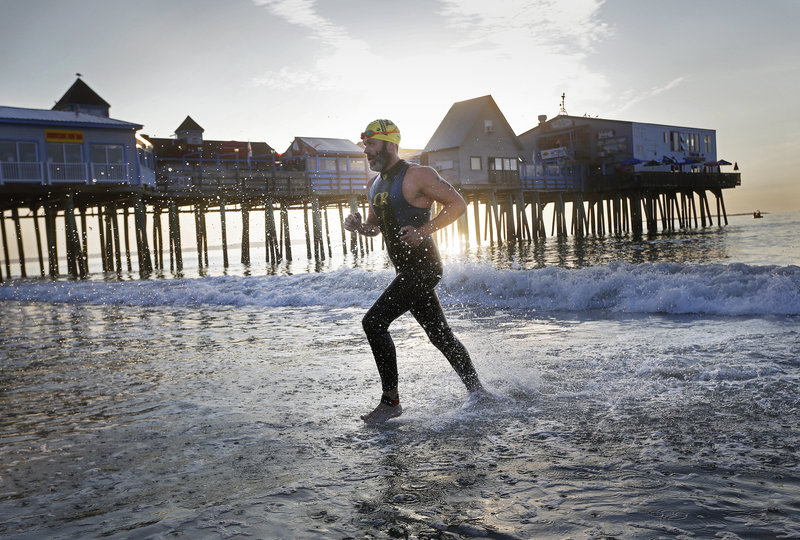 """Vinny Johnson of North Berwick exits the water during the Revolution3 triathlon in Old Orchard Beach on Aug. 26. The Portland Press Herald """"missed the opportunity to focus on the athleticism demonstrated"""" during the event by publishing its coverage in the news pages instead of the sports section, readers say."""