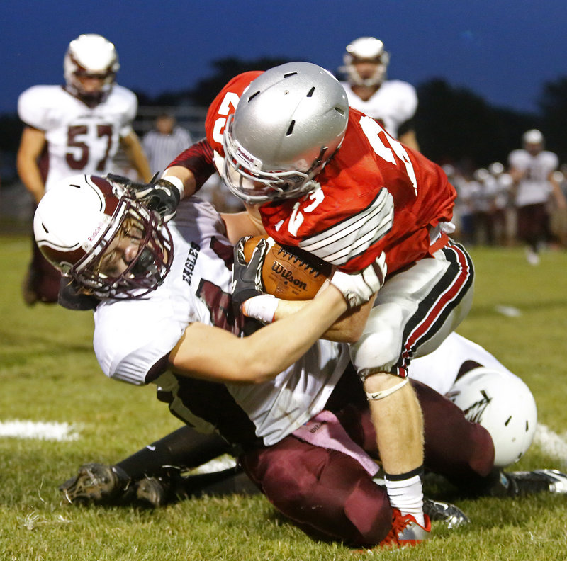 Christian Coons of Windham has the clamps on and won't let go Friday night, bringing down Hayden Owen of South Portland after a reception in the second quarter of Windham's 47-13 victory in a Western Class A opener.