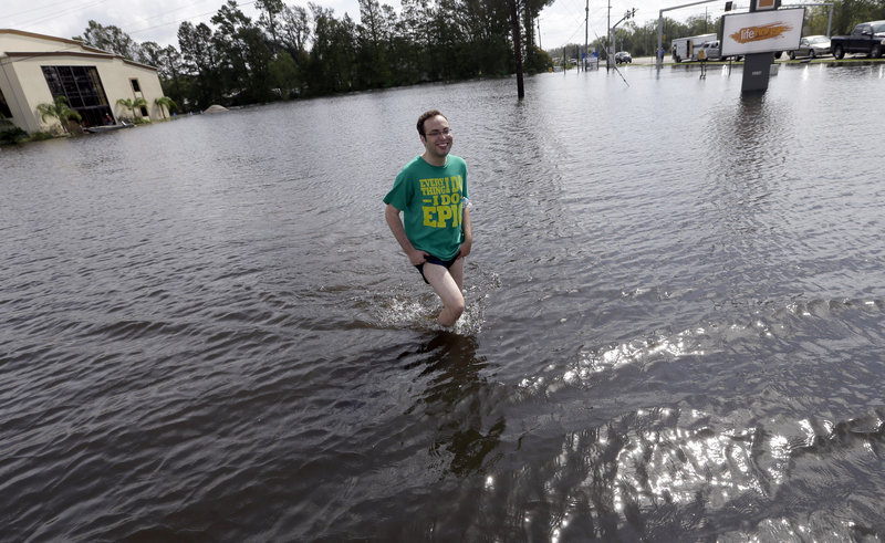 Christopher Keller walks through floodwater Saturday in Reserve, La. More than 400,000 customers remained without electricity in the state in the aftermath of Isaac.