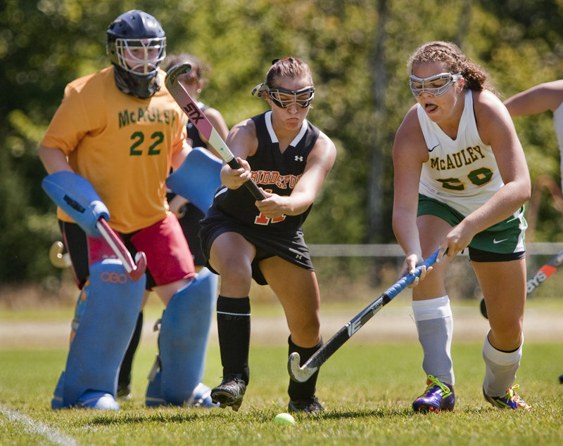 Hana Martinez of McAuley, right, competes with Katie Letellier of Biddeford for a loose ball in front of McAuley goalie Charlotte Murphy.