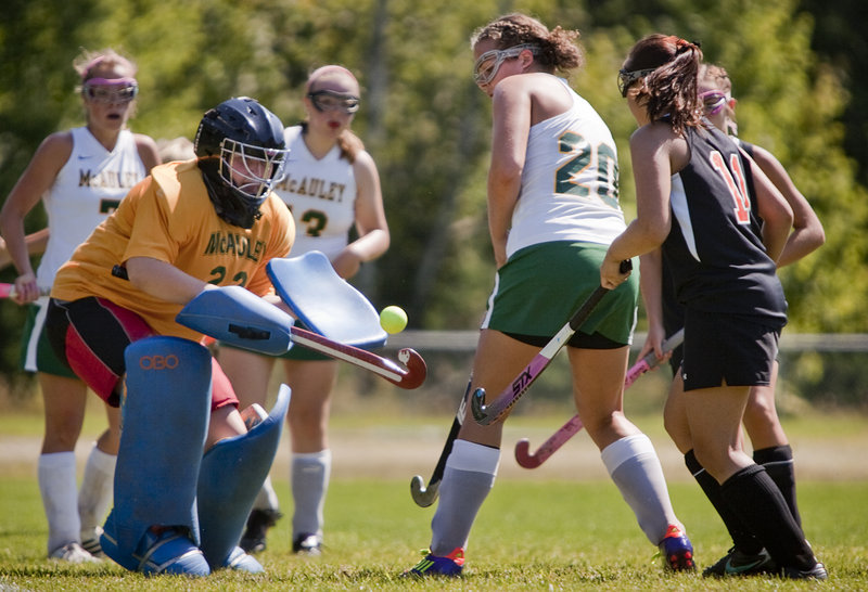 McAuley goalie Charlotte Murphy gets a handle on a loose field hockey ball in front of the net Saturday as teammate Hana Martinez, 20, and Biddeford's Katie Letellier, right, look on. Biddeford came away with a 4-0 victory in Portland.