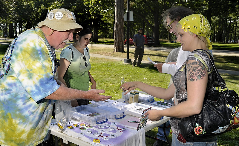 Roger Leisner, left, sells buttons to Lisa Beaudreau of Augusta at the Atlantic CannaFEST at Deering Oaks in Portland on Saturday. Leisner and Hillary Lister, second from left, are members of Medical Marijuana Caregivers of Maine and promote the use of medical marijuana for people who can benefit from it.