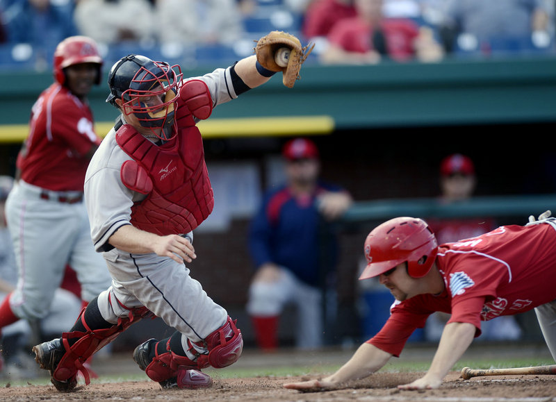 Tag Hulett of the Reading Phillies dives for the plate and beats the tag by Sea Dogs catcher Matt Spring to score a run in the fifth inning Sunday. The Phillies moved closer to clinching an Eastern League playoff berth with a 5-0 win.