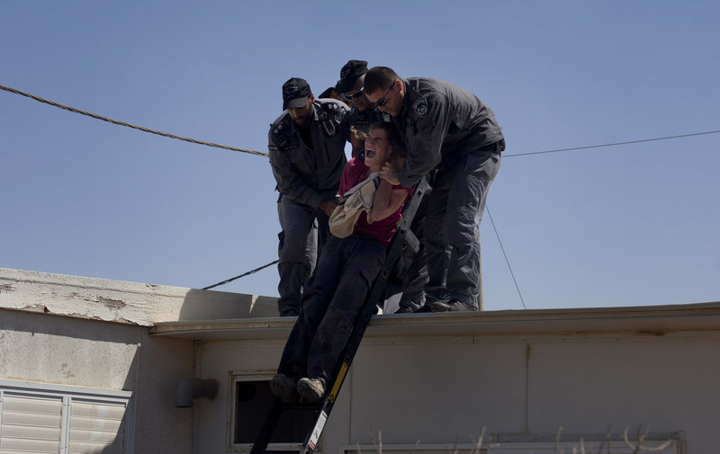 Israeli police officers evacuate a Jewish settler from the roof of a structure in the unauthorized West Bank Jewish settlement of Migron on Sunday. The court-ordered evacuation of Migron culminates years of legal wrangling.