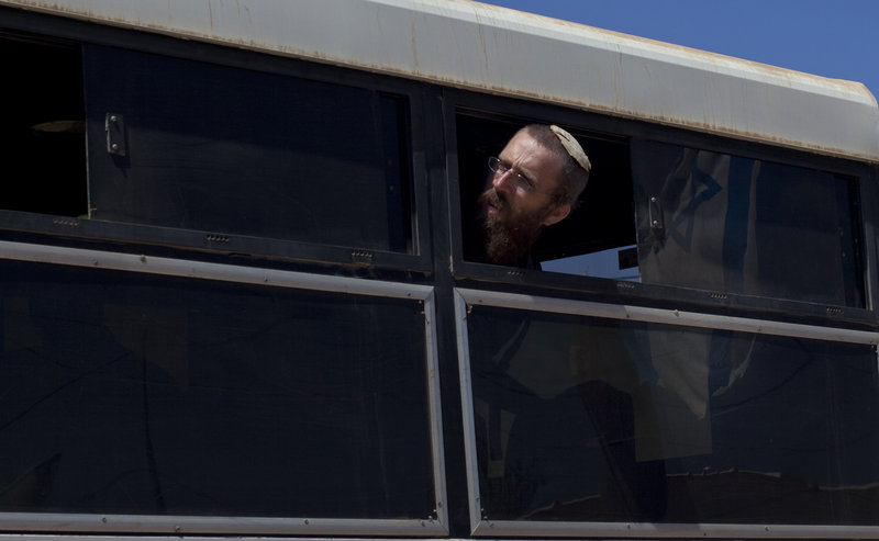 A Jewish settler looks out of a bus window after being evacuated from Migron on Sunday. Migron residents eventually will be relocated to homes a mile from their original site.