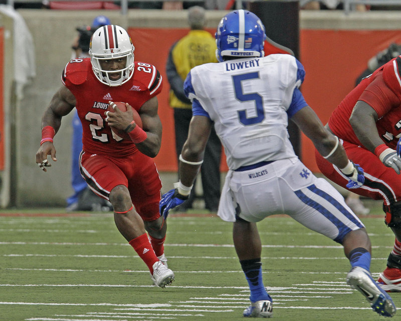 Jeremy Wright of Louisville tries to get past Kentucky's Ashely Lowery during Sunday's game at Louisville, Ky. Wright rushed for three touchdowns in a 32-14 victory.