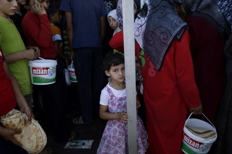 A Syrian girl waits her turn to buy bread and eggs from a store on Monday as she and others take refuge at the Bab Al-Salameh border crossing, near the Syrian town of Azaz, in hopes of entering one of the refugee camps in Turkey.