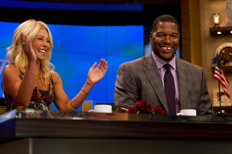 "Former New York Giant Michael Strahan sits with his co-host Kelly Ripa on the set of the newly named ""Live! with kelly and michael"" on Tuesday in New York."