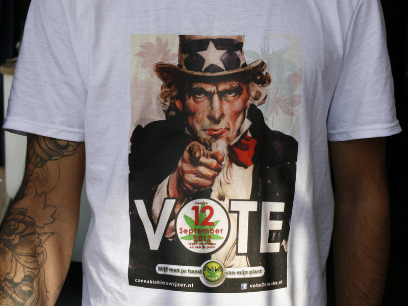 """A T-shirt emblazoned with a modified Uncle Sam-style poster calls on smokers to """"Vote against the weed pass on Sept. 12."""" Under the new system, coffee shops become members-only clubs and only Dutch residents can apply for a pass to get in."""
