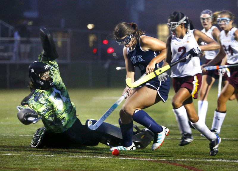 Cape Elizabeth goalie Julianne Ayers slides to stop a scoring bid by Madeline LeRoux of York during their Western Maine Conference field hockey game Tuesday night. York emerged with a 2-1 victory on a goal by Taylor Simpson.