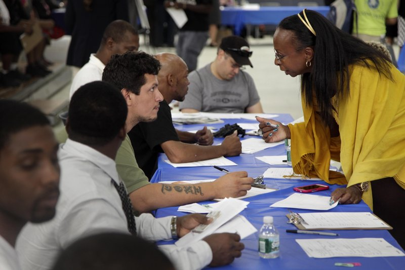 Job seekers fill out applications at a job fair in New York. Unemployment is still over 8 percent, but down from 10 percent in 2010. Will voters go with the number, or the trend, in November?