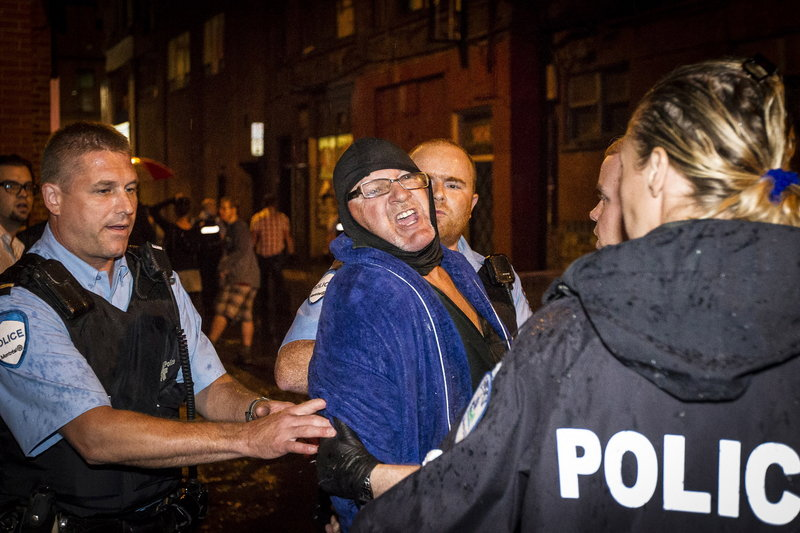 Police arrest a man outside the Parti Quebecois victory rally in Montreal on Wednesday after a masked gunman wearing a blue bathrobe opened fire, killing one person and wounding another.