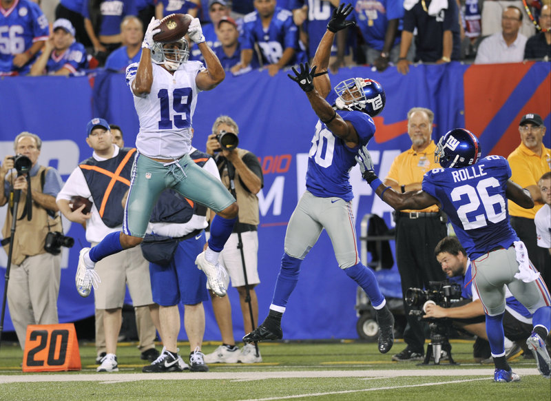 Miles Austin of the Dallas Cowboys hauls in a touchdown pass Wednesday night as Justin Tryon, 30, and Antrel Rolle defend for the New York Giants during the Cowboys' 24-17 victory in the league opener.