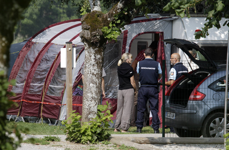 Investigators stand at the campsite where several people were methodically killed. French officials are finding international links tying the slain family to Britain, Iraq and Sweden.