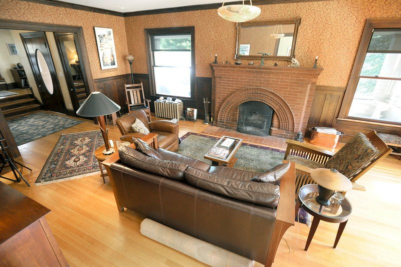 The living room, with its reproduction wallpaper, wainscoting and one-of-a-kind fireplace
