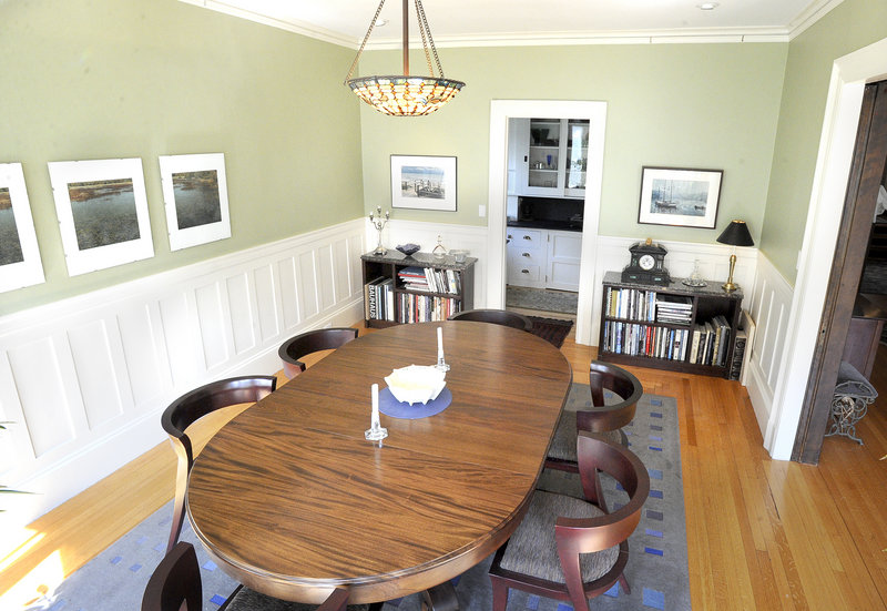 The bright dining room, with wood floors and white wainscoting