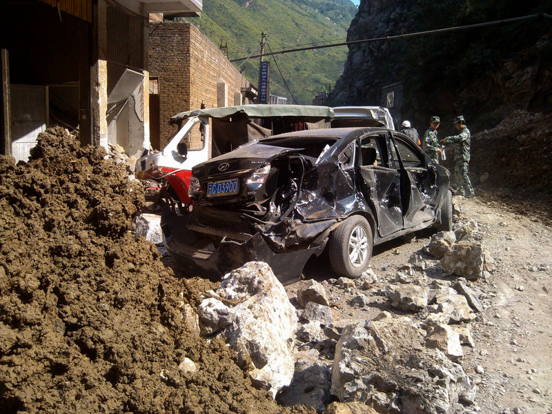 Damaged cars are seen in Luozehe town, Yiliang County, southwestern China's Yunnan Province, on Friday in this photo provided by China's Xinhua News Agency. A series of earthquakes collapsed houses and triggered landslides.