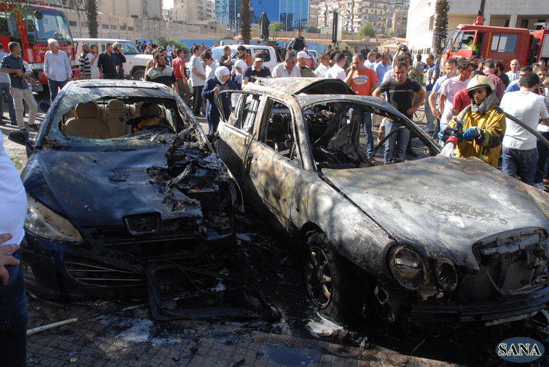 A firefighter extinguishes a burned car close to where an explosion went off between the Ministry of Information and the Ministry of Justice in Damascus, Syria, on Friday.