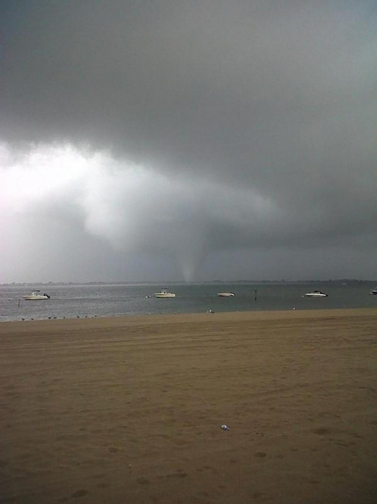 A funnel cloud forms over the Breezy Point section of the Rockaway peninsula in the Queens borough of New York on Saturday. No serious injuries were reported.