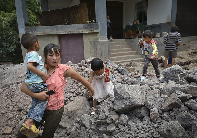 A woman and children flee earthquake damage in Luozehe township in hardest-hit Yiliang County in southwest China's Yunnan province Saturday. Two quakes hit Friday.