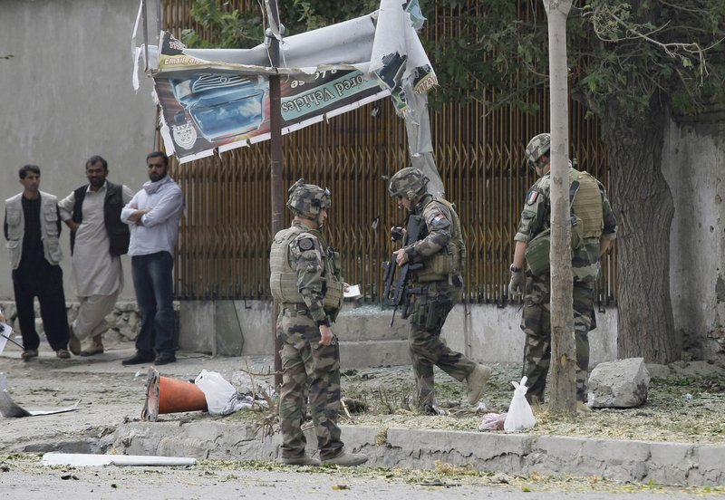French soldiers, who are part of NATO forces, investigate the scene of a suicide attack Saturday in Kabul, Afghanistan. Police estimated the bomber to be about 14 years old.