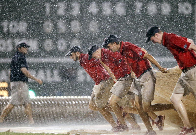Members of the Fenway Park grounds crew pull the tarp onto the field during one of the two rain delays Saturday night. The Red Sox lost to Toronto, 9-2.