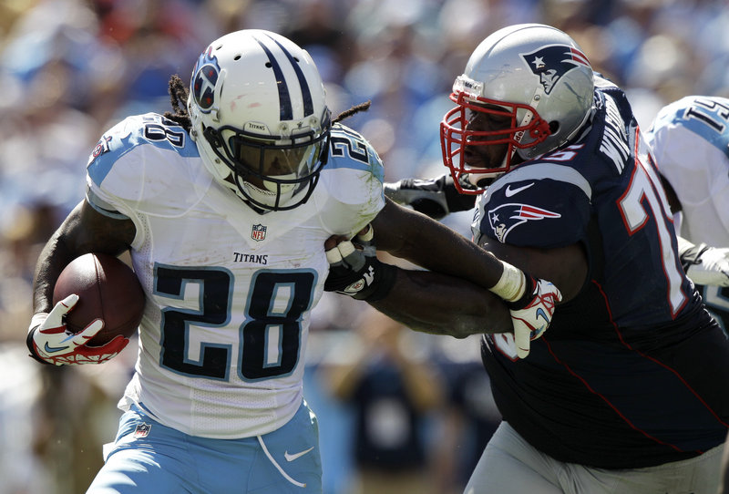 Vince Wilfork chases down Titans running back Chris Johnson, who gained just 4 yards on 11 carries Sunday against a Patriots defense rejuvenated by the addition of rookies Chandler Jones, Dont'a Hightower and Tavon Wilson.