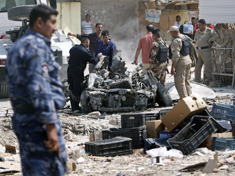 Security forces inspect the scene of a car bomb attack in Basra, Iraq, one of at least 13 cities that suffered bombings or shootings Sunday. The worst violence was in the capital, where bombs pounded a half-dozen neighborhoods much of the day.