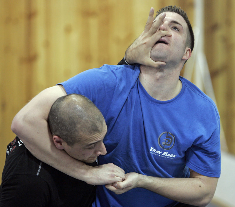 Kurt Lakatos, left, and fellow instructor John Urbanek demonstrate a move during a Krav Maga self-defense training class in Brookfield, Wis.
