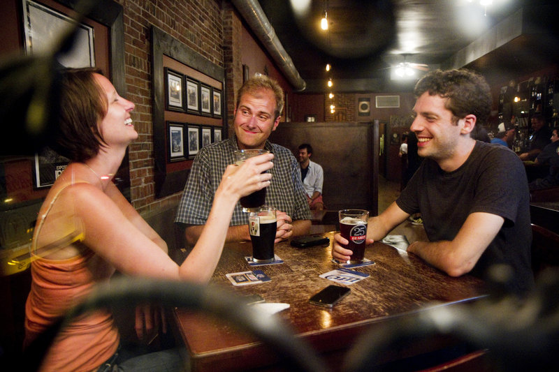 Ashley Hanamann, Bryan McLeod and Ethan Jud, all of Portland, chat over beers at The Snug.