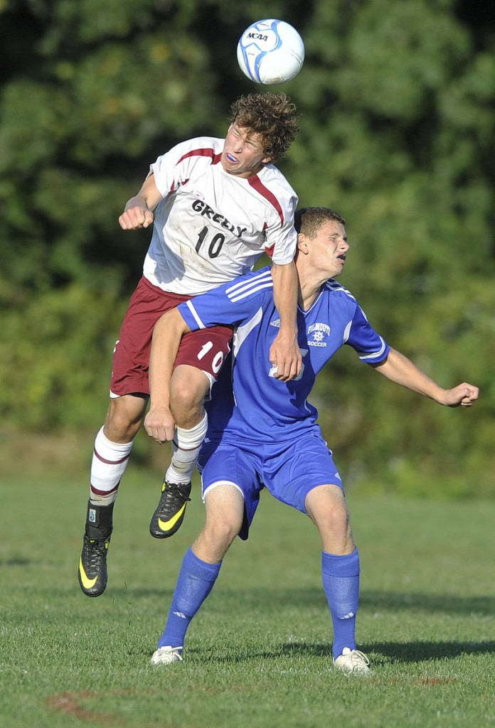 Greely's Matt Crowley leaps over a Falmouth player for a head ball during Falmouth's 3-2 overtime win at Cumberland on Tuesday.