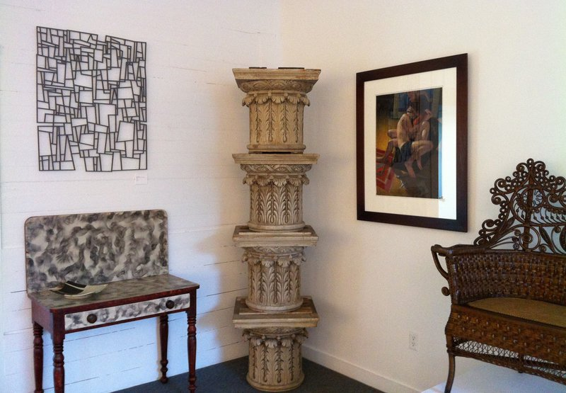 """Wall Drawing – Rocks and Trees"" by Portland artist Leon Anderson hangs above a smoked grained card table from W.M. Schwind Jr. Antiques of Yarmouth. Also pictured are four stacked capitals from Smith-Zukas Antiques of Wells. To the right of the columns is a pastel painting by Kate Doyle, ""The Embrace,"" from ""Accord VIII"" at the George Marshall Store Gallery."