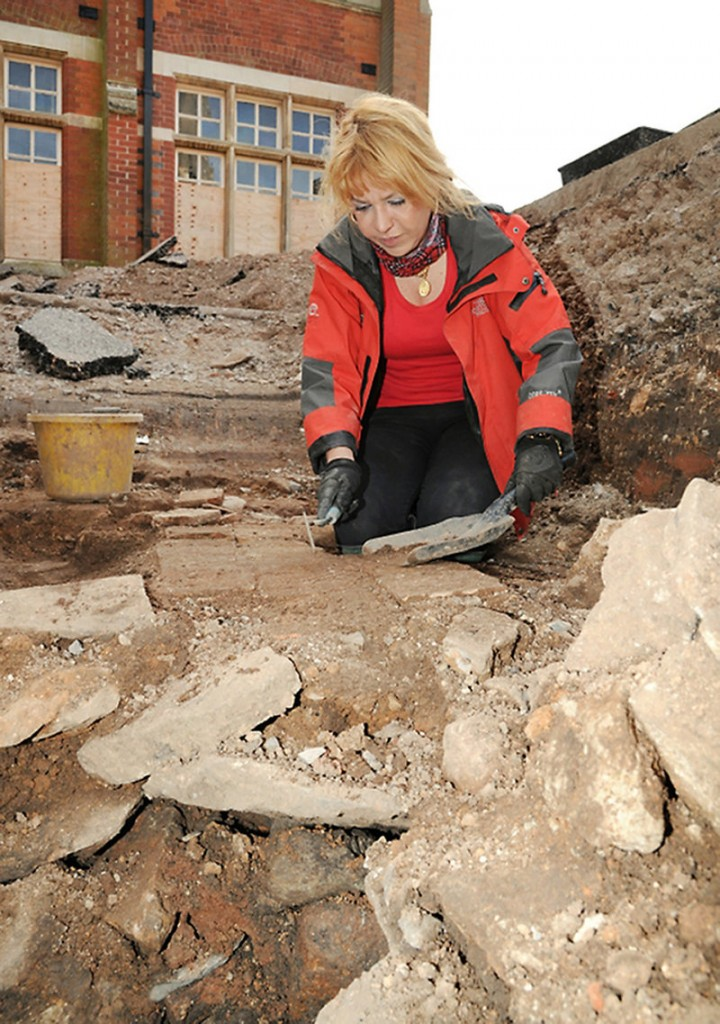 Karen Ladniuk of the Richard III Society cleans a path made of reused medieval tiles during an excavation in Leicester, England, seeking the lost grave of King Richard III. Bones unearthed during the dig have been sent for DNA testing.