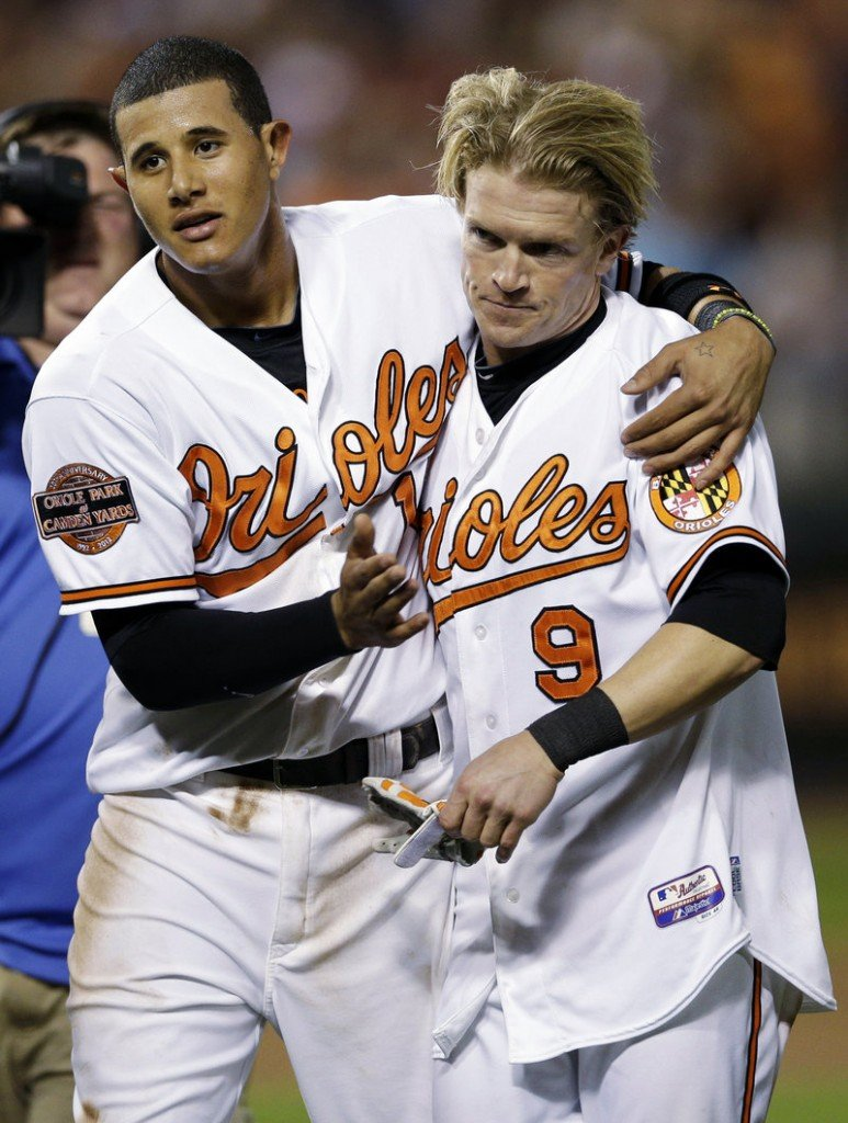 Manny Machado, left, celebrates with Nate McLouth after scoring the winning run on McLouth's single in the ninth inning Wednesday night against Tampa Bay.