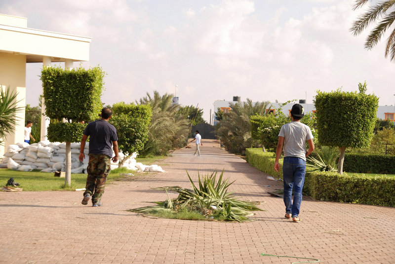 Libyans walk on the grounds of the U.S. consulate in Benghazi, Libya, after a militant attack Tuesday left four Americans dead, including Ambassador Chris Stevens, 52.