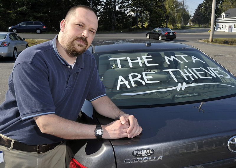 """Joe Thibeault, a commuter from Saco, displays a statement on his car's back window expressing his anger over the new toll system that goes into effect Nov. 1. """"I was shocked,"""" Thibeault said in response to the increase he faces."""