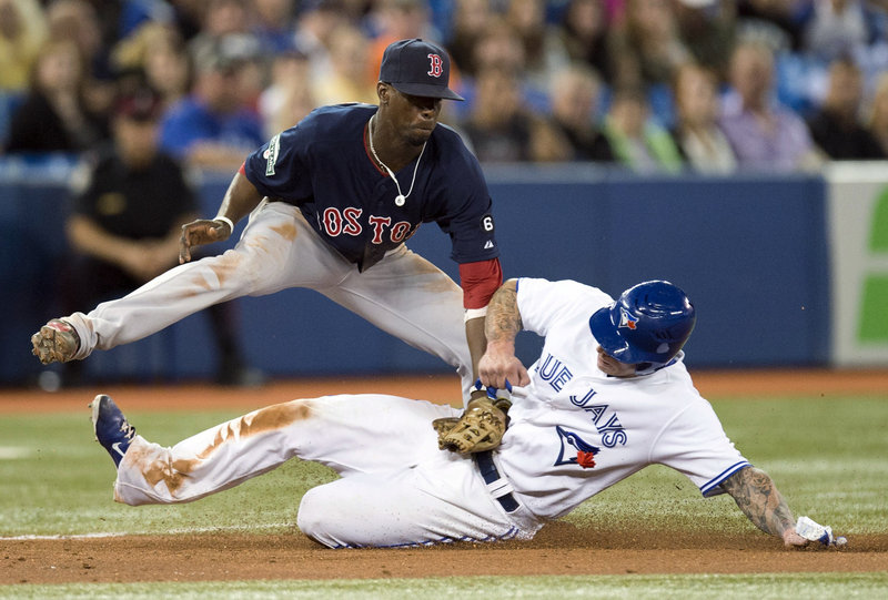 Boston's Pedro Ciriaco tags Toronto's Brett Lawrie at third base in the eighth inning of an 8-5 win by the Red Sox at Toronto Friday. The Red Sox blew an early 5-3 lead, coming back to snap a six-game losing streak against Toronto.