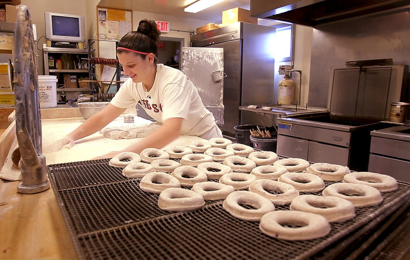 """Emily Bachelder, a baker at Tony's Donuts in Portland, gathers flour while making blueberry cake donuts. A new Tony's Donuts will open soon in South Portland. """"During the hard economic times, the bakery business is always good,"""" says Rick Fournier, Tony's owner."""