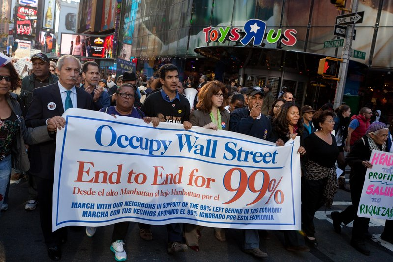 "Occupy Wall Street protesters walk through Times Square on Nov. 7, 2011. On Monday, the formation of a ""people's wall"" around the New York Stock Exchange is planned to mark a year since the occupation of a park near Wall Street."