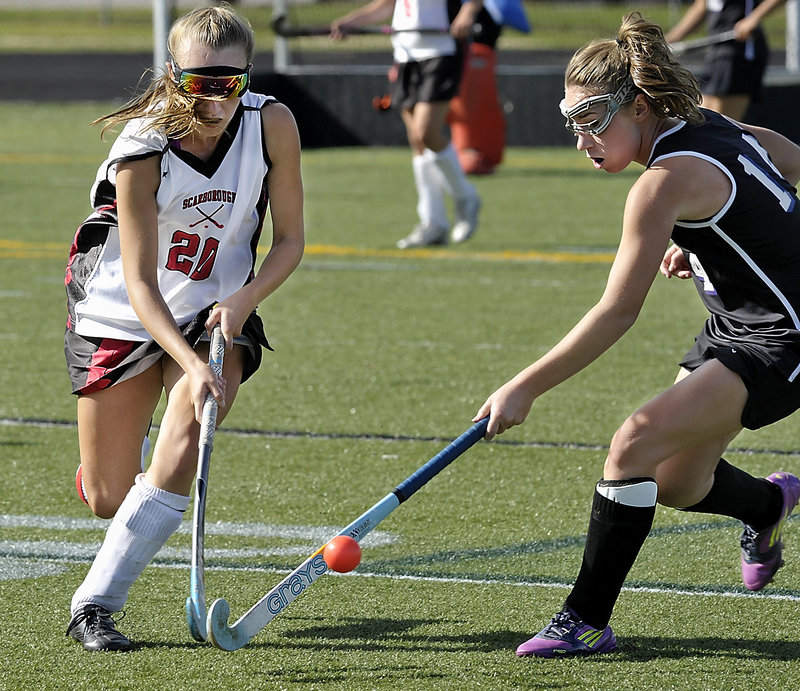 Grace Whelan, left, of Scarborough battles with Ashley Tice of Marshwood during a clash of unbeaten field hockey teams Saturday. Scarborough won, 1-0.