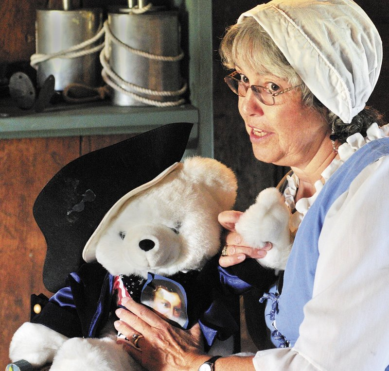 """Bonnie Wilder, a member of the Daughters of the American Revolution, talks about a Patrick Henry toy bear as she begins her """"Meet the Framers of the Constitution"""" program that was part of the events at Old Fort Western in Augusta on Saturday."""