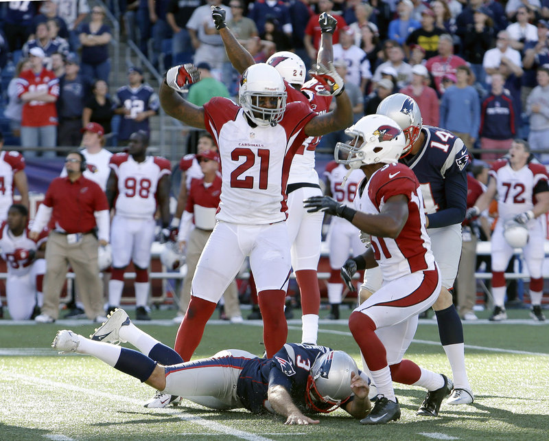 Arizona players celebrate after Stephen Gostkowski, bottom, missed a 42-yard field goal with one second remaining, enabling the Cardinals to hold on for a 20-18 win over the Patriots.