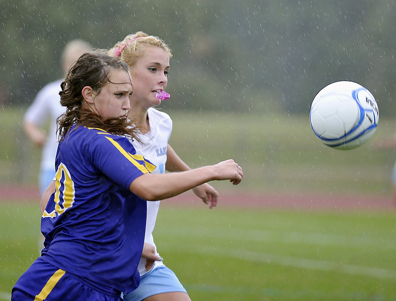 Eden Monsen of Cheverus, foreground, races Melissa Morton of Windham for a loose ball in the rain Tuesday during unbeaten Windham's 3-1 victory in girls' soccer.