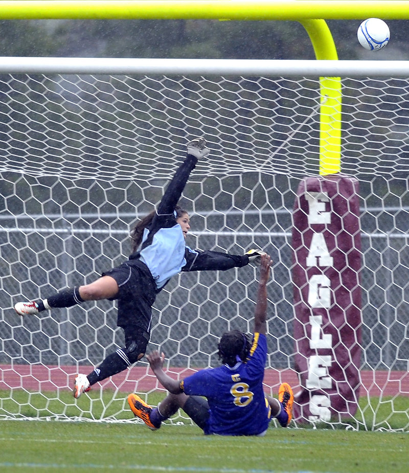 Windham goalkeeper Kate Kneeland, blocks a shot over the goal post as Sadie Lyons of Cheverus slides in Tuesday during Windham's 3-1 girls' soccer victory at home.