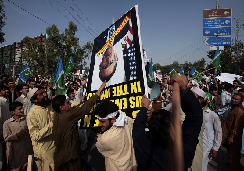 Protesters strike a poster bearing a portrait of U.S. President Barack Obama near the U.S. consulate in Peshawar, Pakistan, on Tuesday. Hundreds of protesters broke through a barricade outside the consulate, sparking clashes with police that left several wounded on both sides, police said.