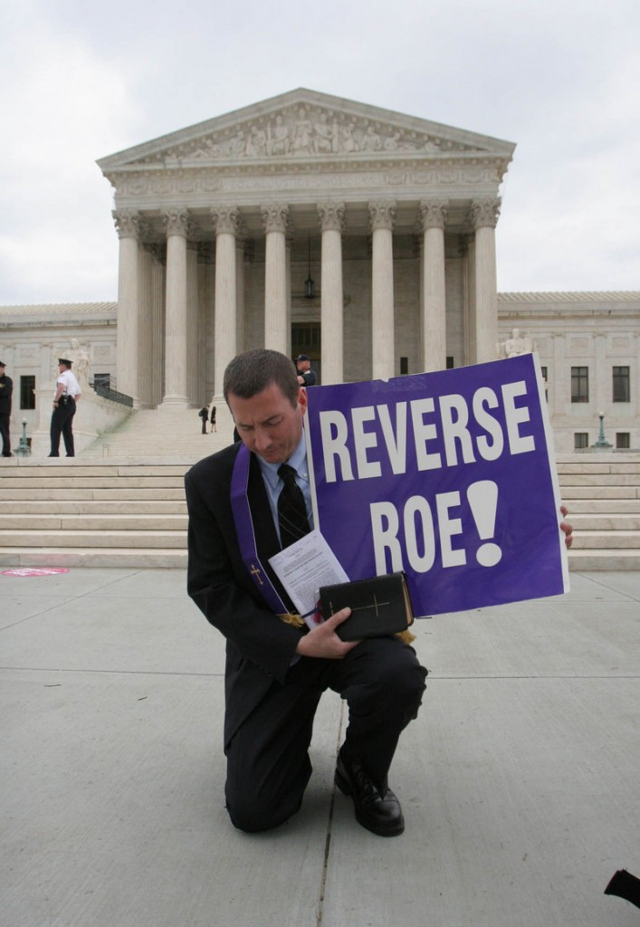 An abortion rights opponent protests in front of the U.S. Supreme Court in Washington. A reader says many who think life begins at conception want to force that belief on everyone.