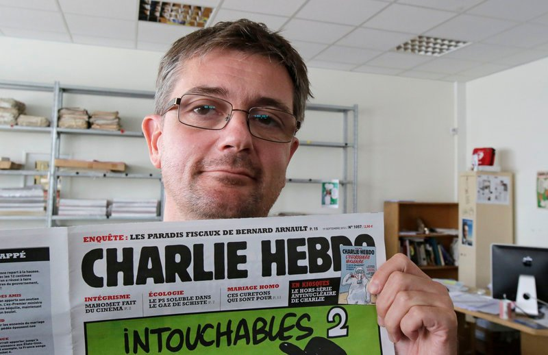 Stephane Charbonnier, who goes by Charb, displays a copy of the satirical French weekly Charlie Hebdo in Paris Wednesday. He is the chief editor or the newspaper.